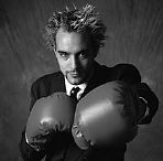 Man in a business suit with boxing gloves uid 1381497