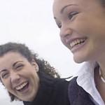 Giggling women standing on edge of water uid 1283622