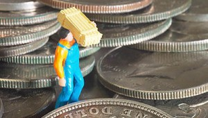 Miniature workman carrying load through pile of silver American coins uid 1172264